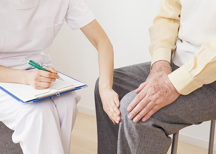 患者の膝に手を当てるスタッフ